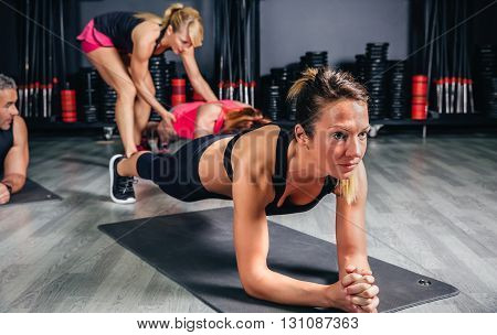 Portrait of blonde woman doing push ups while trainer correcting position of other woman in the background