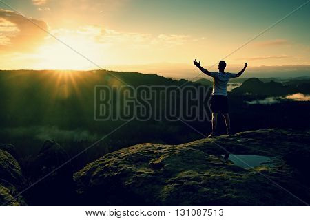 Runner On The Peak. Man In His Target Gesture Triumph With Hands In The Air. Crazy Man In Black Pant