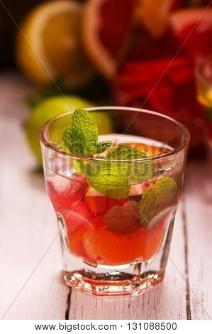 Glass of summer drink with citrus fruits, ice and mint. Selective focus