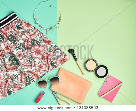 Fashion urban summer outfit, girl clothes set, cosmetics, makeup accessories. Stylish handbag clutch, trendy pink dress, necklace, sunglasses. Woman essentials. Unusual overhead, top view on blue