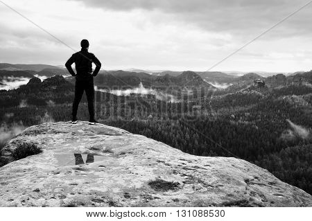 Slim Tall Tourist On Sharp Peak Of Rock In Rock Empires Park Is Watching Over Misty And Foggy Mornin