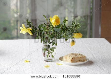 puff pastry with cream and a bouquet of yellow roses