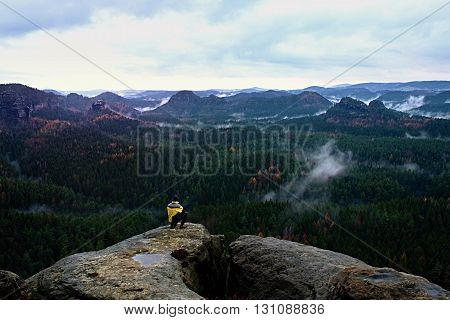 Rear View Of Tall Hiker In Yellow Black Jacket On Rocky Peak While Enjoying A Daybreak Above Fall Mo