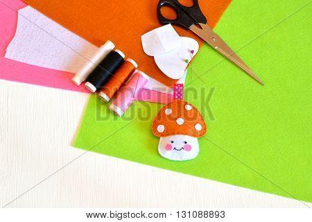 Felt toy mushroom, thread, needle, scissors. Tutorial. Do it yourself concept