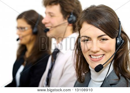 Three young customer service operators sitting in a row and talking on headset. Selective focus on women in front. Isolated on white background.