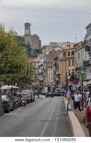 FRANCE CANNES - AUGUST 8 2013: View of the tourist street in the old town and Notre Dame de l'Esperans.