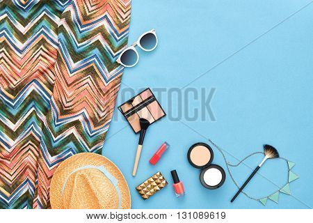 Fashion stylish clothes, cosmetics, makeup accessories set. Urban summer girl colorful outfit. Stylish handbag clutch, trendy pants, necklace, sunglasses. Woman essentials. Unusual overhead, top view