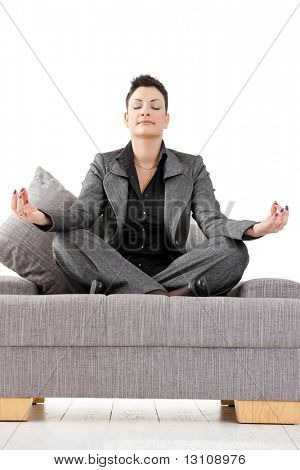 Young businesswoman sitting on sofa relaxing in yoga meditation pose. Isolated on white background.