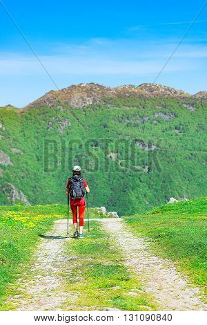 On the mountain road girl walks on a pilgrimage alone