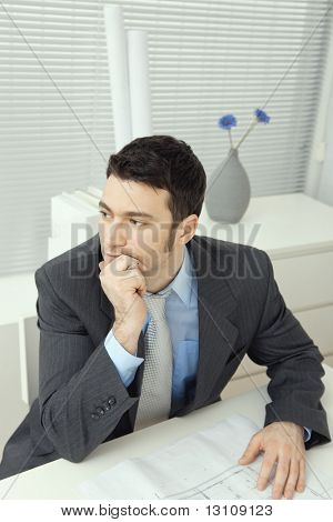 Architect wearing grey suit sitting at office desk, thinking over floor plan. Overhead shot.