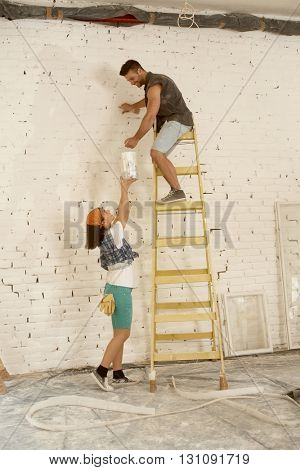Young couple renovating home, man painting wall on top of ladder, woman lifting painting can up.