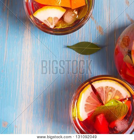 Refreshing summer cocktails with citrus fruits over blue vintage background. Top view