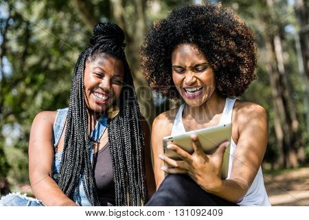 Afro friends using tablet in the park