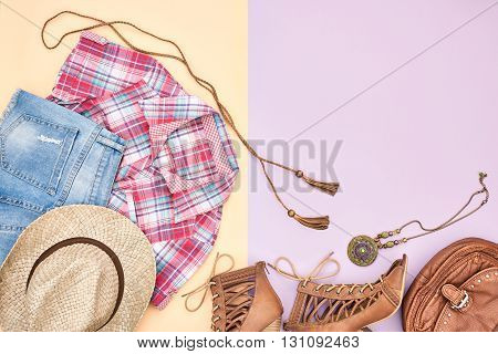 urban country creative outfit. cowboy street style fashion girl clothes accessories set. hipster woman, trendy plaid shirt, denim shorts, shoes, straw hat necklace. overhead, top view on pink yellow