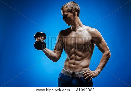 The fit young man with beautiful torso on blue background doing exercise with dumbbell