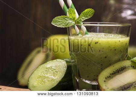Glass of green refreshing smoothie with kiwi, cucumber and apple. Toned image. Selective focus