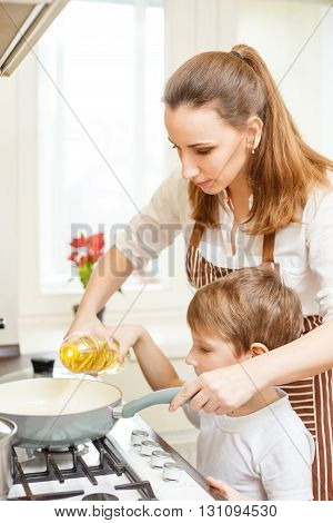 Young woman using pan on cooker together with her son. Family cooking background