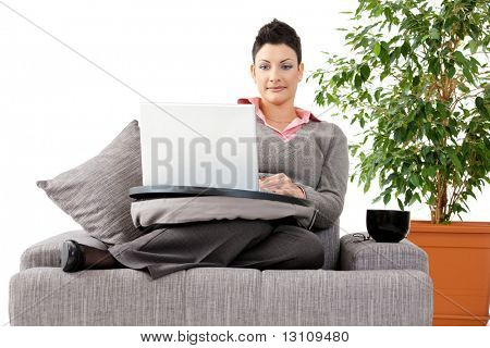 Young woman sitting on couch working on laptop computer at home, smiling. White background with green plant.