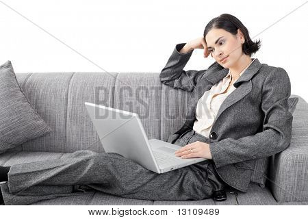 Young businesswoman sitting on sofa, working with laptop computer. Isolated on white background.