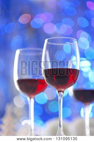 Wineglasses on blue blurred lights background