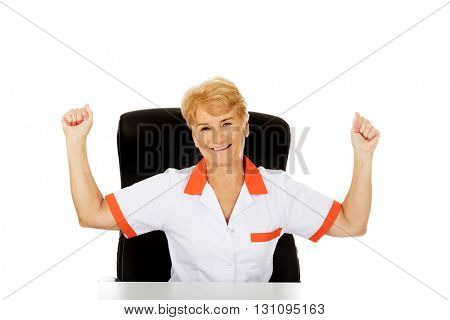 Happy elderly female doctor or nurse sitting behind the desk withd hands up