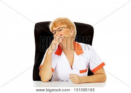 Tired elderly female doctor or nurse sitting behind the desk and yawns