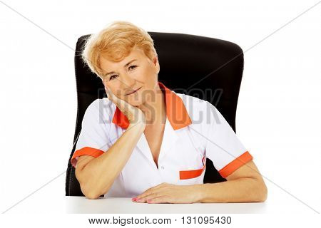 Smile elderly female doctor or nurse sitting behind the desk leaning on hand