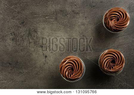 Three chocolate cupcakes on grey background