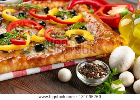 Freshly homemade pizza on wooden table closeup