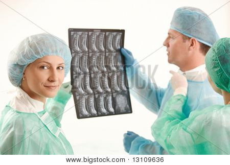 Medical team examining x-ray image, female doctor smiling at camera.?
