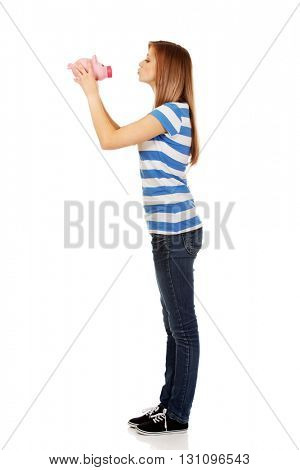 Happy teenage woman kissing piggybank