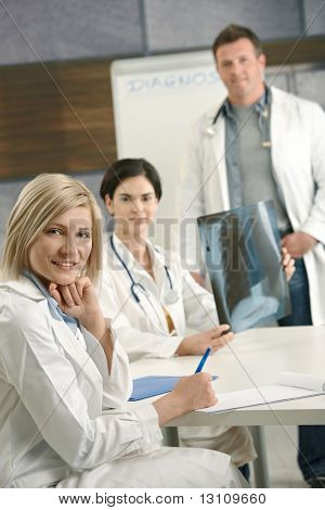 Portrait of medical doctors consulting about x-ray image, looking at camera, smiling.?