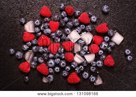 Ripe blueberry and raspberry with ice cubes over black wet stone background. Toned image. Selective focus