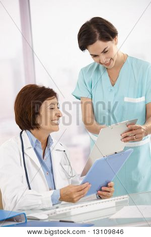 Smiling medical expertise sitting at desk, doing paperwork with assistant.?