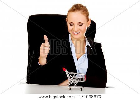 Smile business woman with shopping cart on the desk