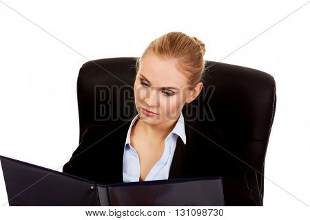 Beautiful business woman sitting on armchair and reading notes