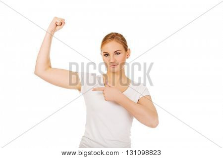 Funny young woman showing her muscles
