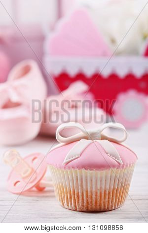 Tasty cupcake with bow and baby shoes, decorative baby carriage on color background