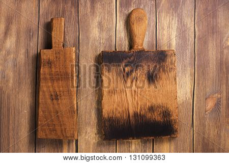 Vintage cutting board on rustic wooden background. Top view. Vintage style, toned image