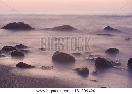 Summer seasonal natural vacation background. Romantic morning at sea. Big boulders sticking out from smooth wavy sea. Pink horizon with first hot sun rays. Long exposure.