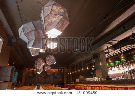 Modern interior of restaurant. Lamps are hanging over the big wooden table