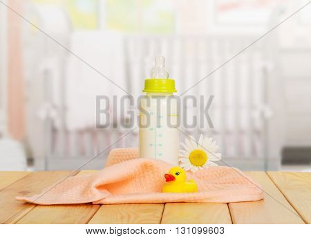 Baby bottle of milk, a towel and a rubber duck on the background of the kitchen.