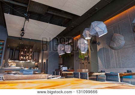 Interesting interior in modern restaurant. Tables and chairs are creating contrast with contemporary lamps