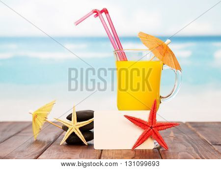 Blank card, a glass of orange cocktail and a starfish on a background of the sea.