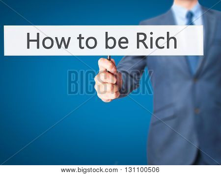 How To Be Rich - Businessman Hand Holding Sign