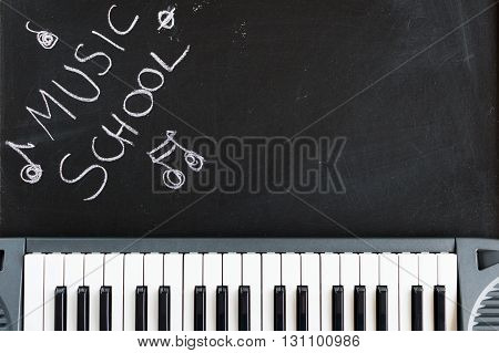 Music keyboard on blackboard background for music school children with copy space