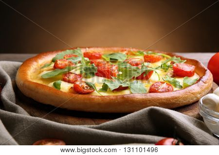 Pizza Margherita with arugula on brown background