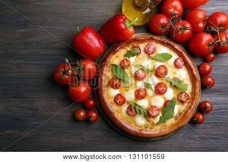 Pizza Margherita with arugula, red pepper, tomatoes on wooden table