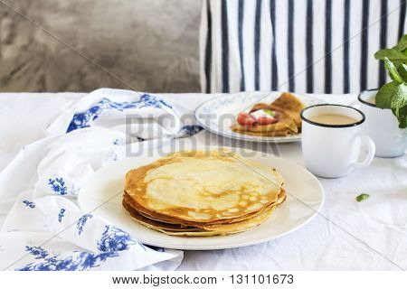 Stack of hot crepes over kitchen table, sunny morning breakfast. Selective focus, space for text. Toned image