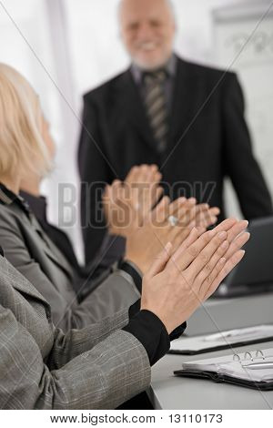 Clapping hands in closeup focus on businessmeeting, senior businessman standing in background.?